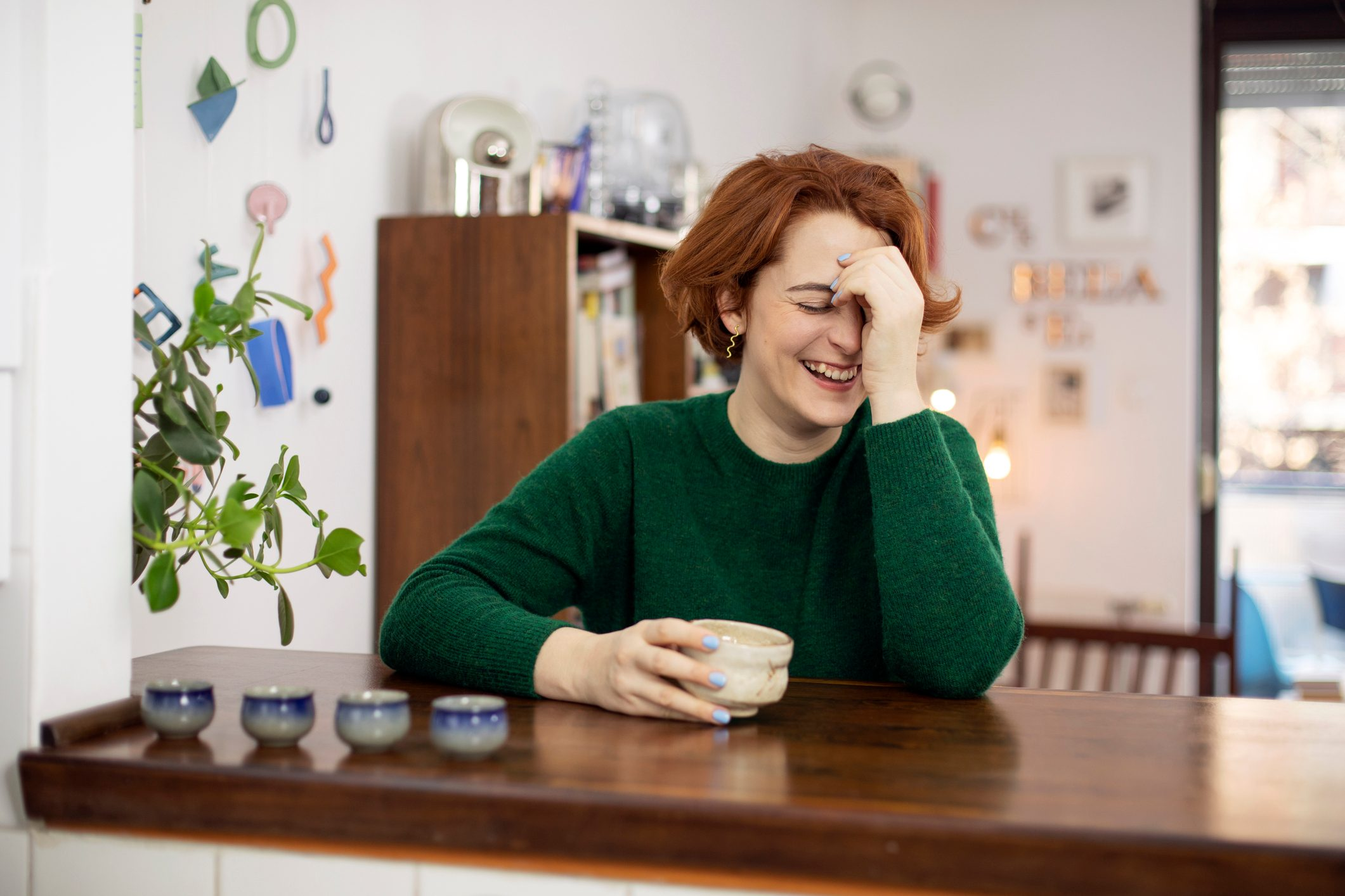 woman laughing at home drinking tea