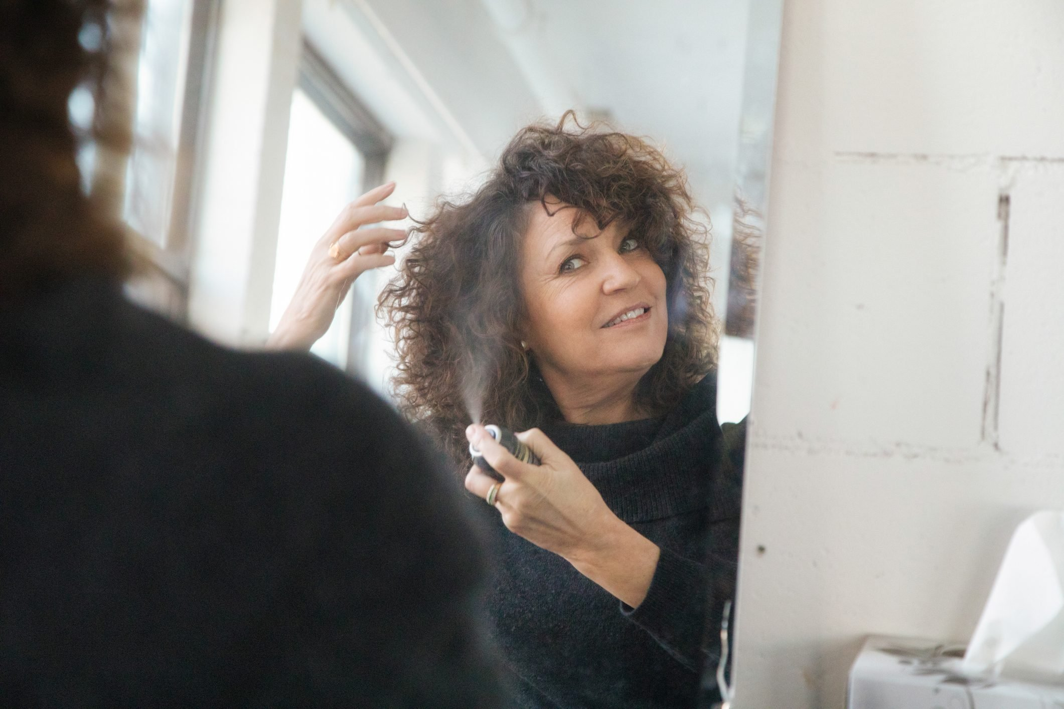 Mature woman applying hair spray in front of mirror