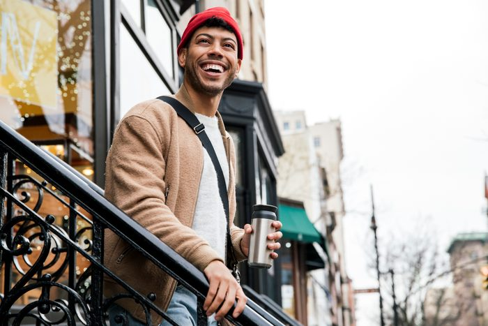 Smiling young man walking down stairs in city