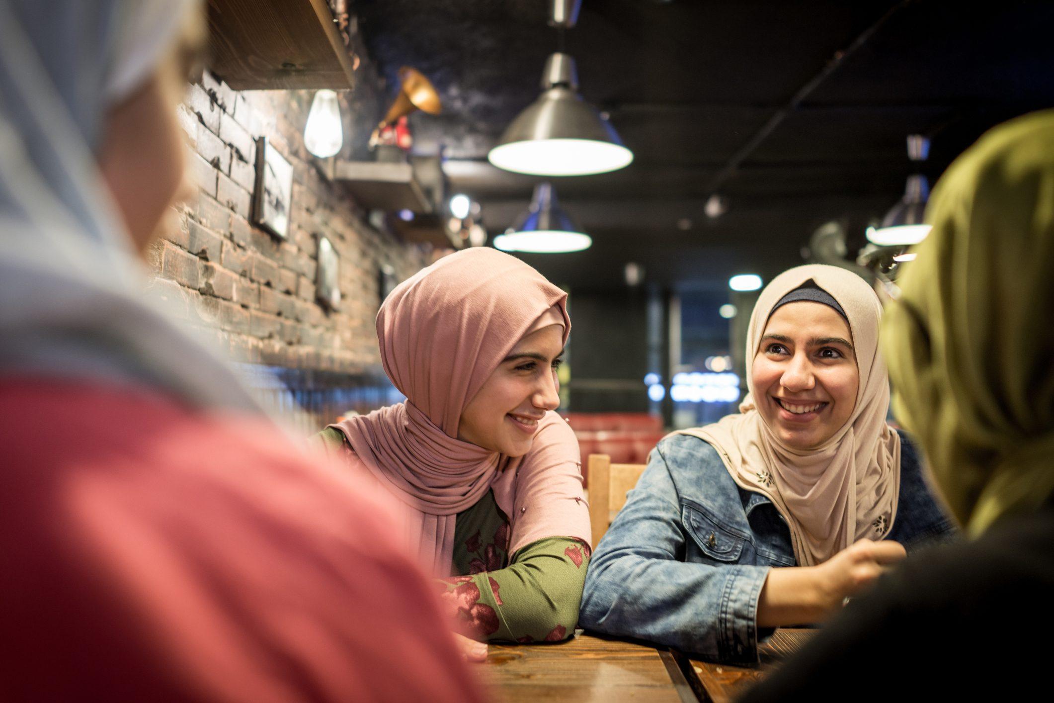Arab teenage girls having fun together in restaurant