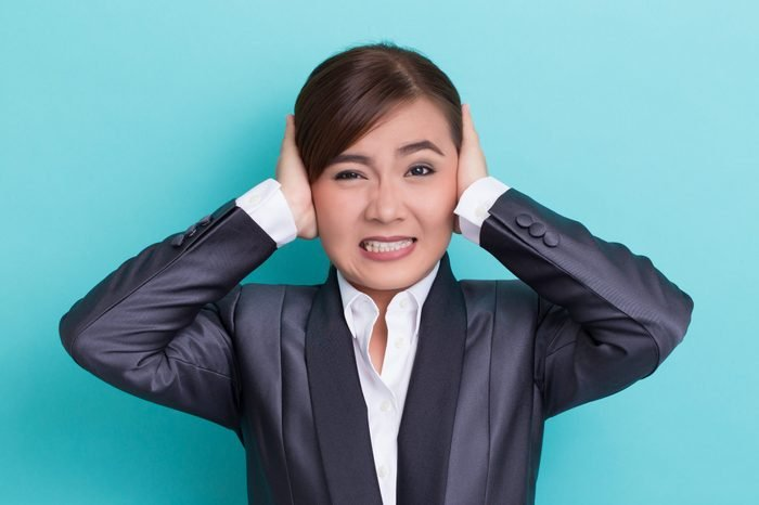Businesswoman Covering Ears While Standing Against Blue Background
