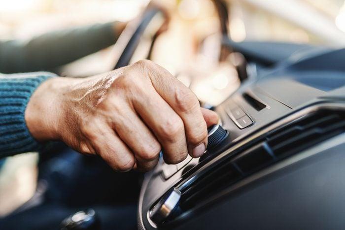 Close up of senior man changing radio station while sitting in his car.