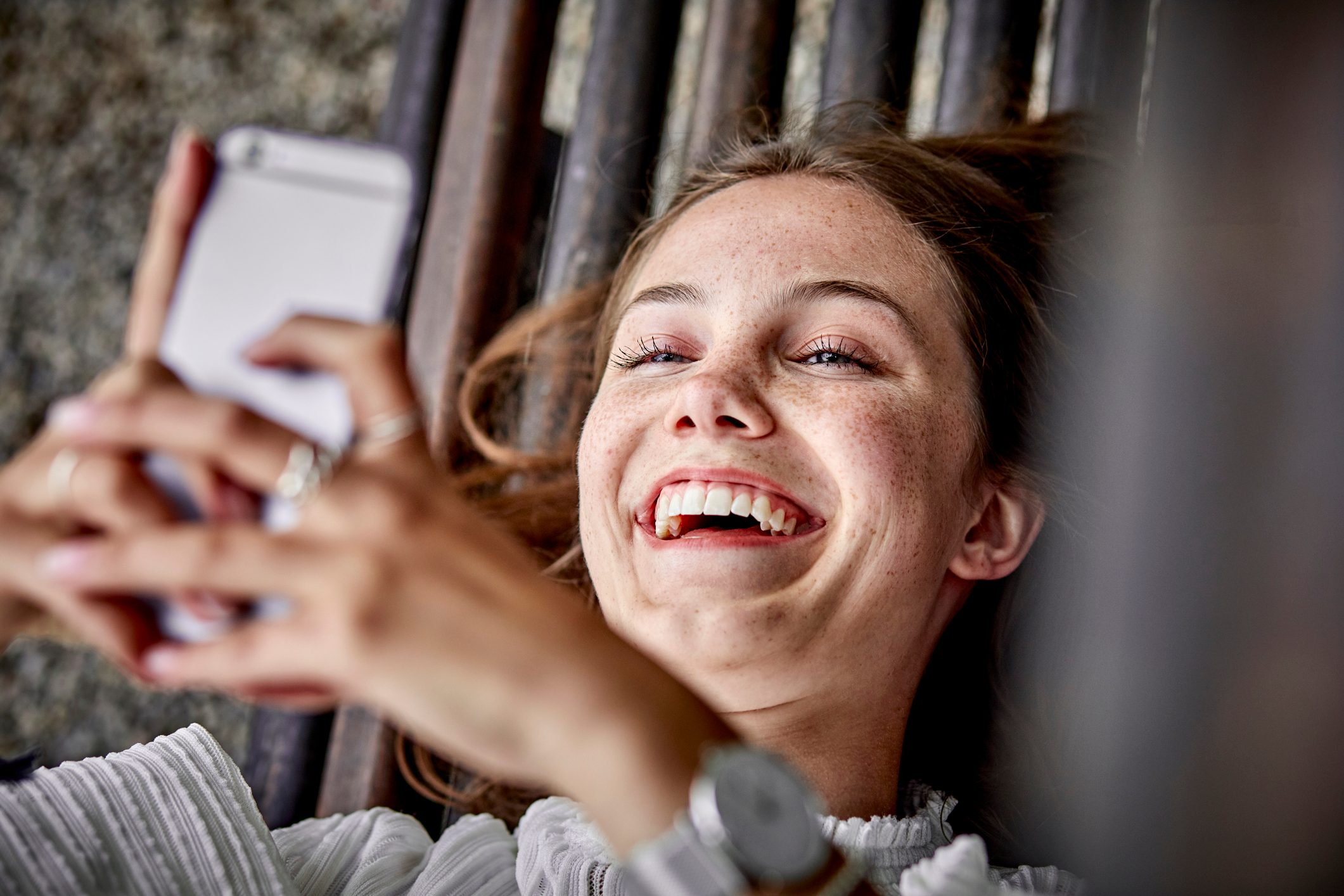Laughing young woman lying on a bench using cell phone