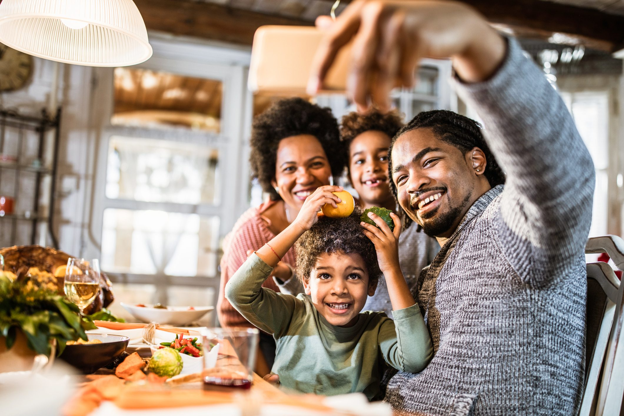 Happy black family taking a selfie with cell phone in dining room.