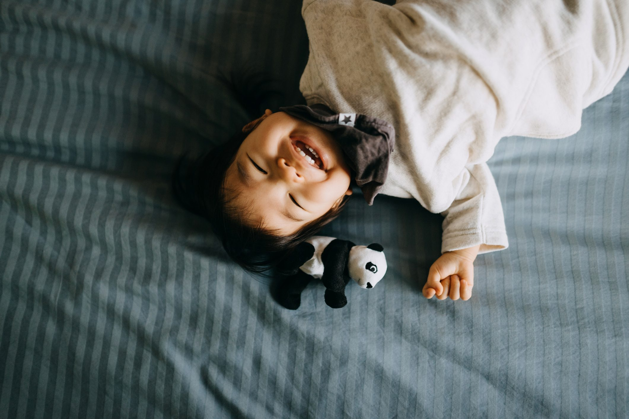 Portrait of cute little Asian toddler girl laughing joyfully and lying on bed with her panda soft toy lying next to her