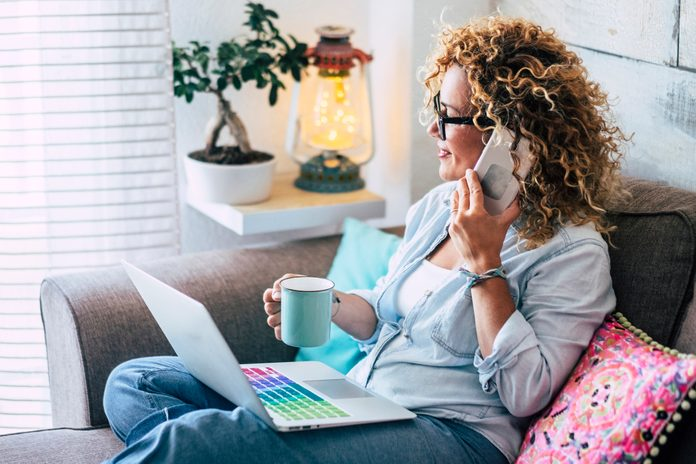 Woman on couch at home with coffee mug, laptop and cell phone