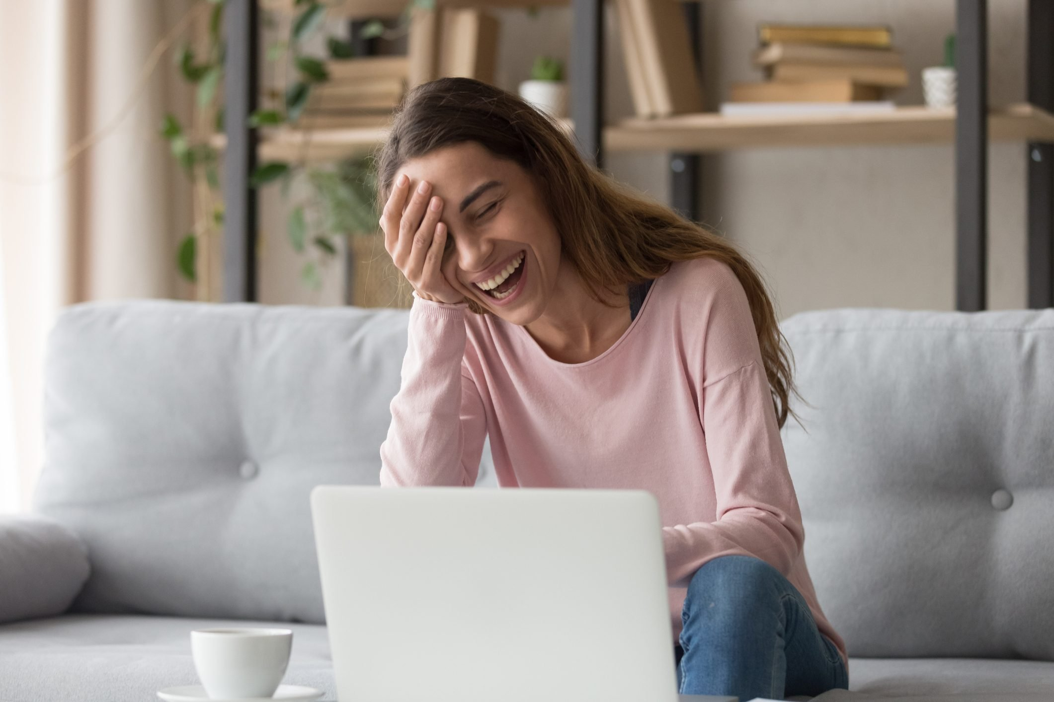 Laughing woman sitting on couch watching comedy movie on laptop