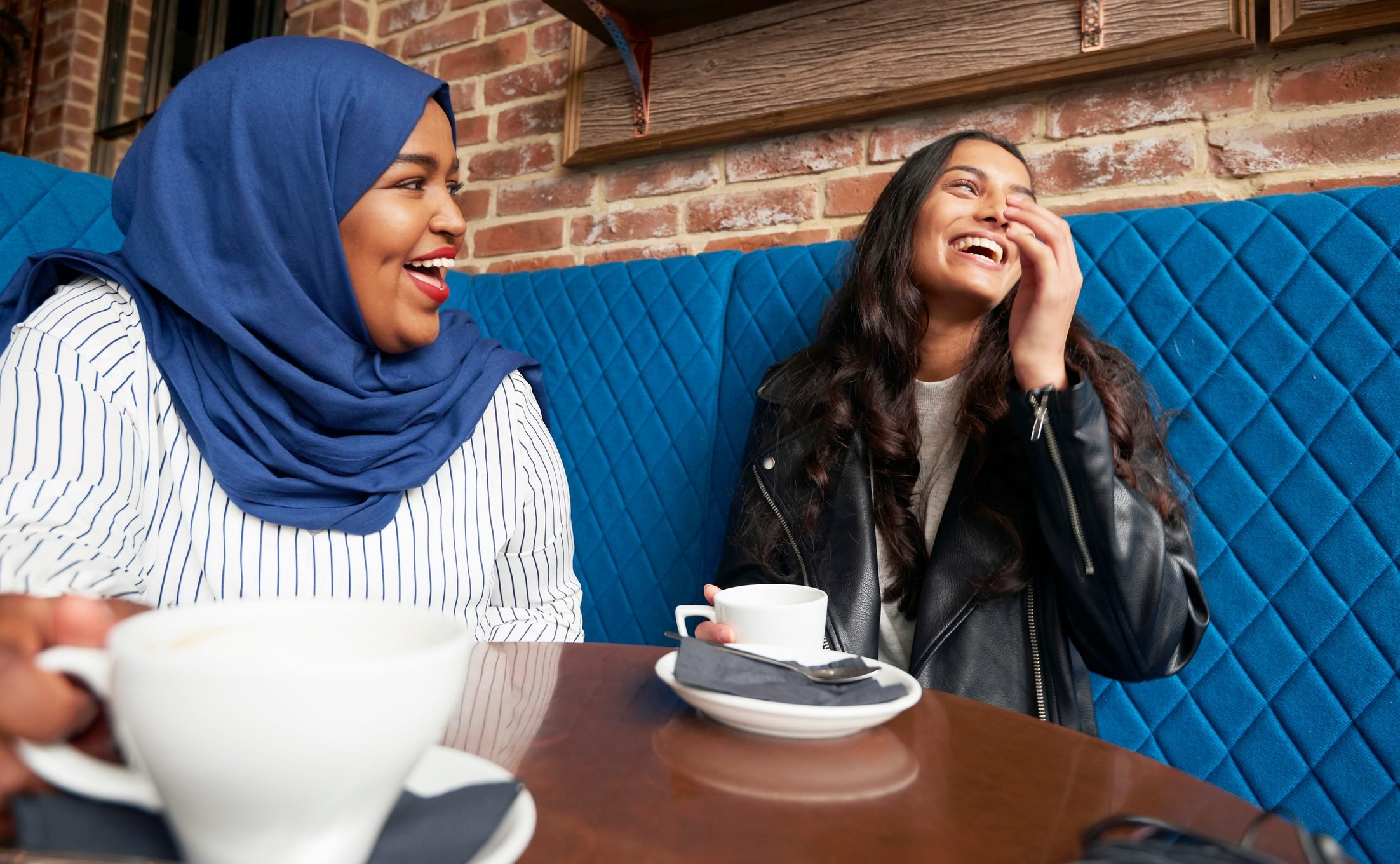 Friends laughing and drinking coffee in a cafe