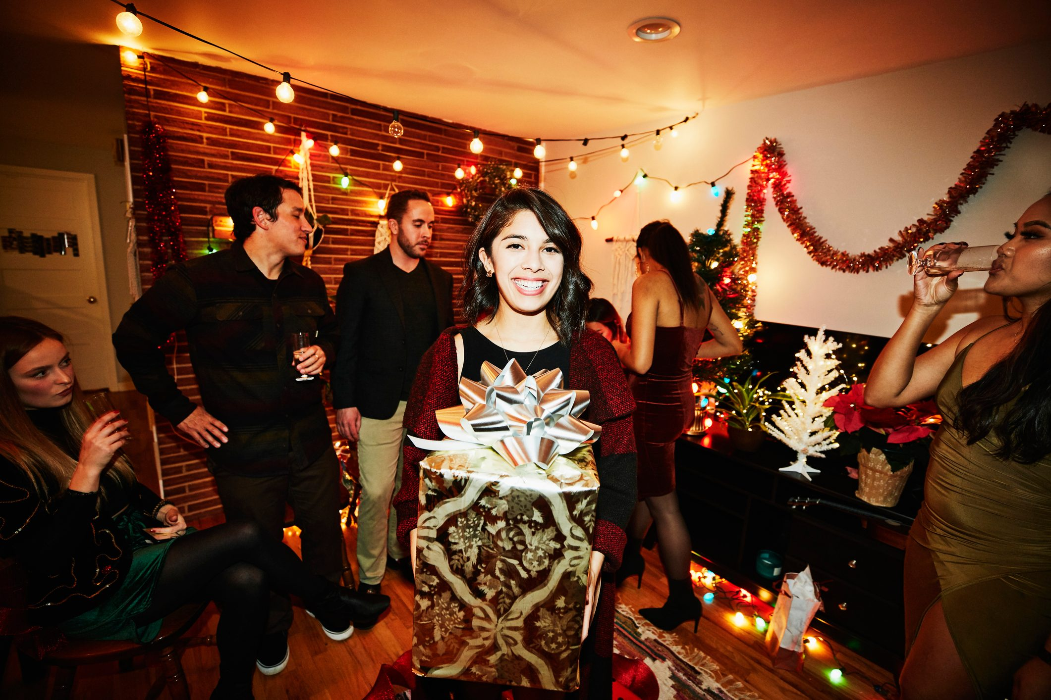 Smiling woman holding present during holiday party with friends in home