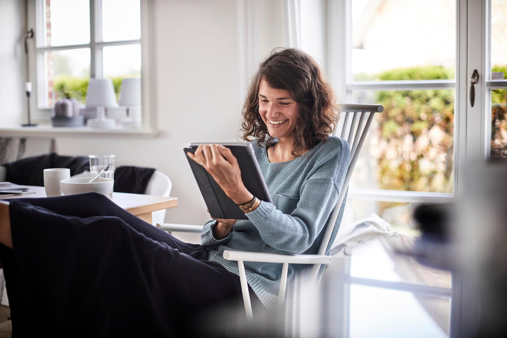 Relaxed young woman sitting at table using tablet