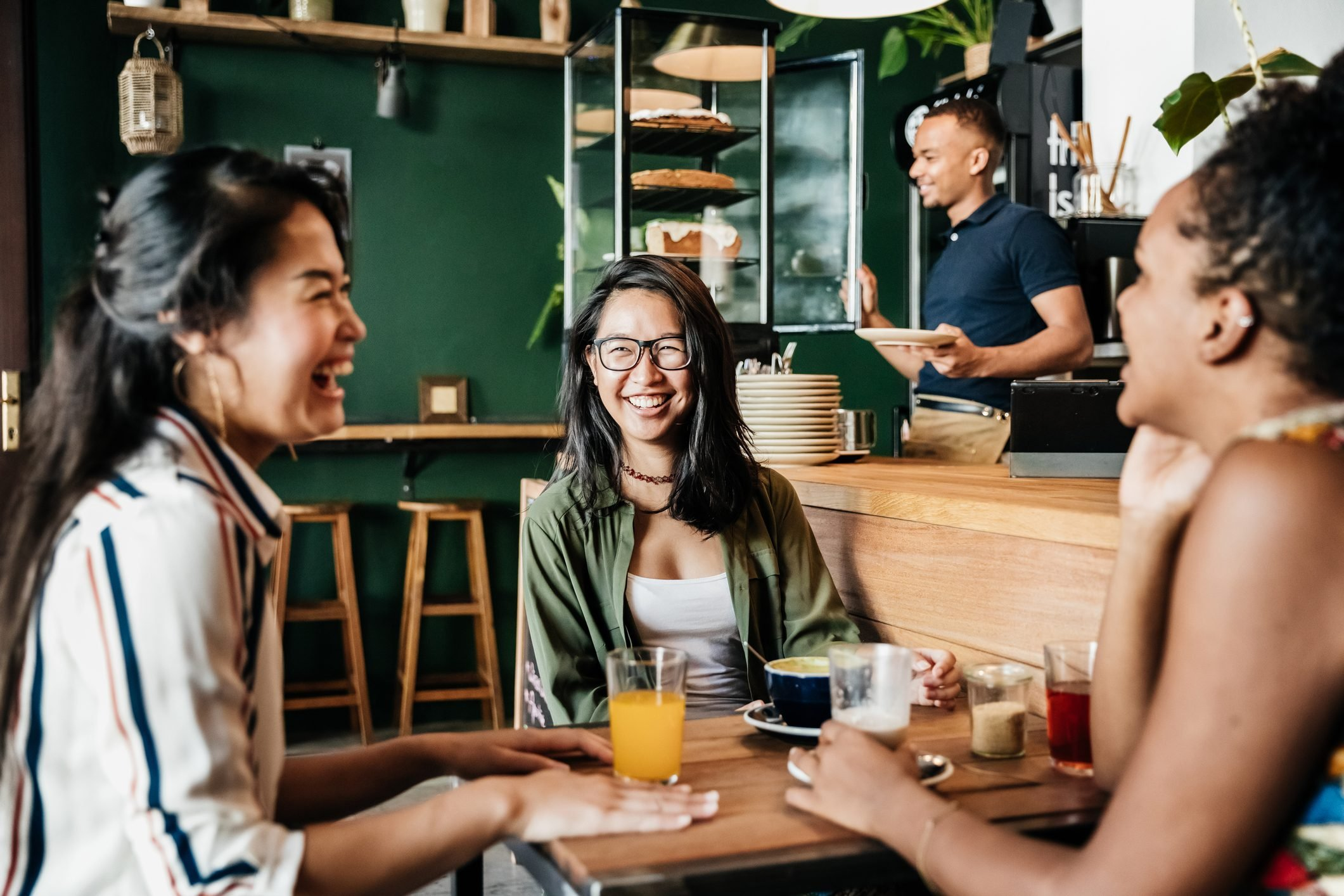 Three Friends Laughing At Chatting In Coffee Shop