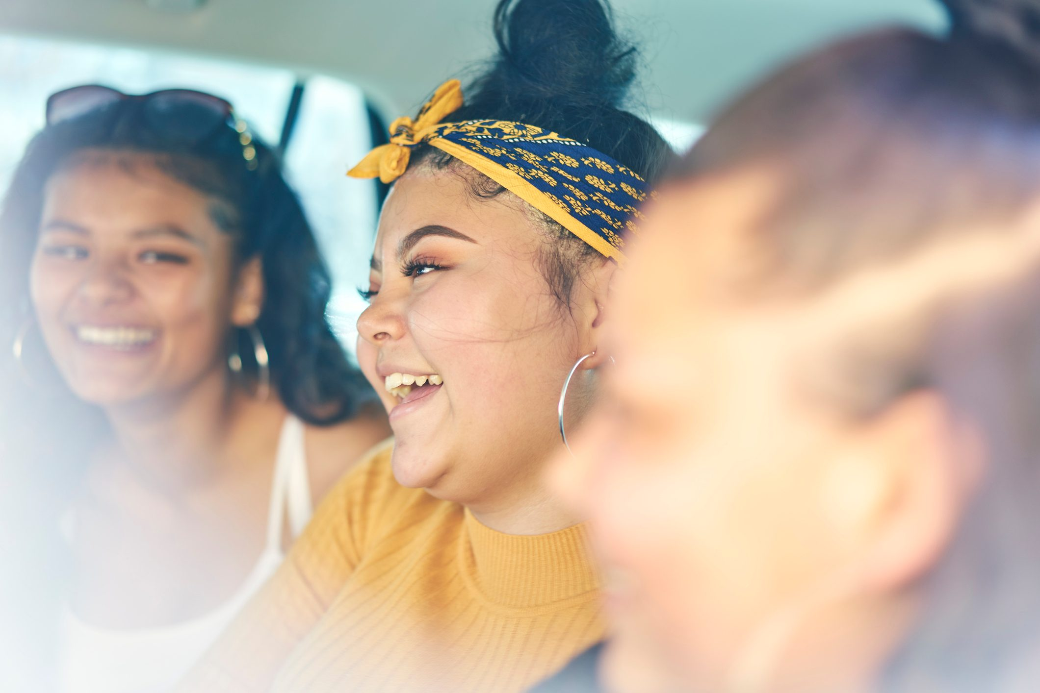 Young woman with teenage sisters in car back seat laughing, close up