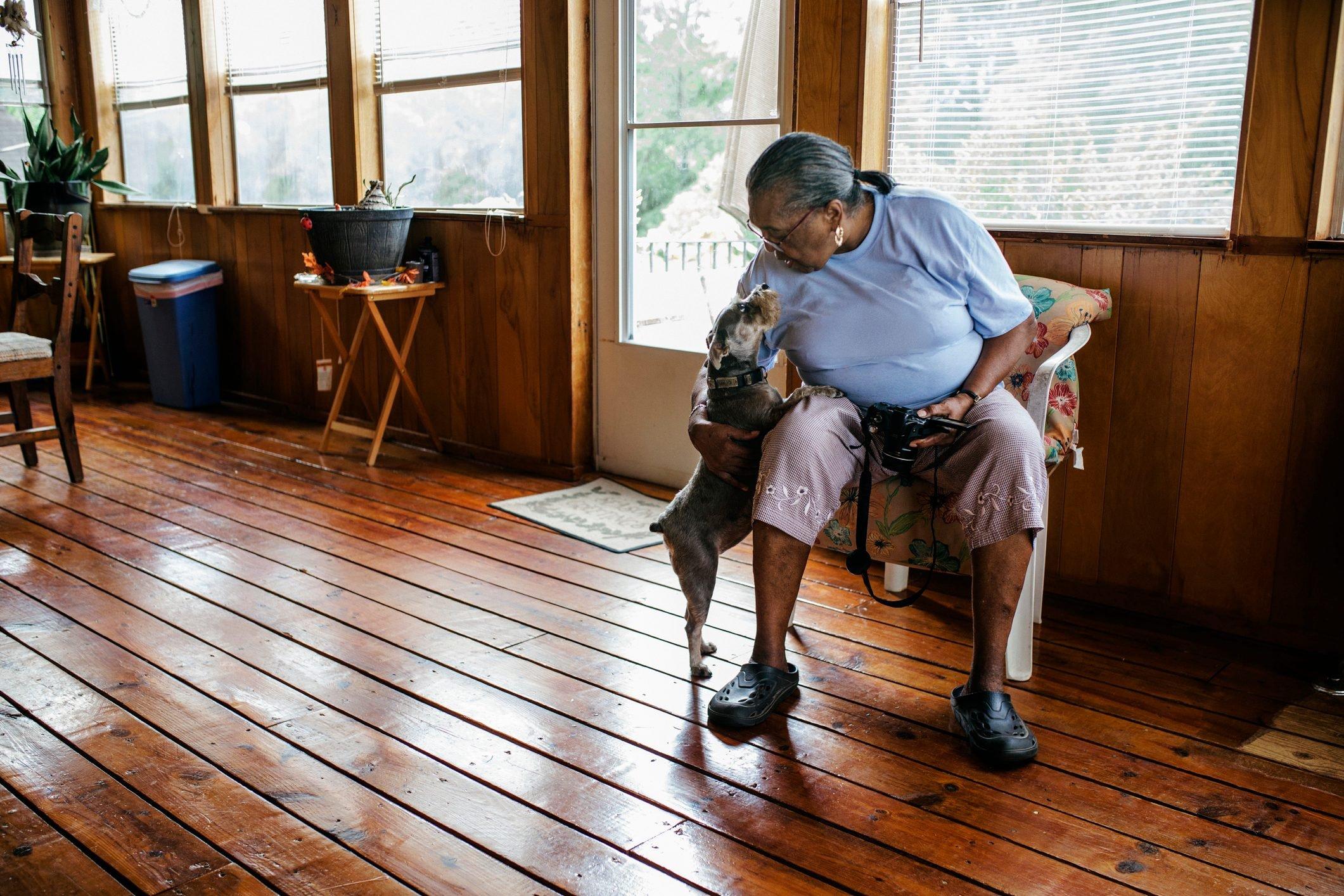Senior black woman patting the family dog