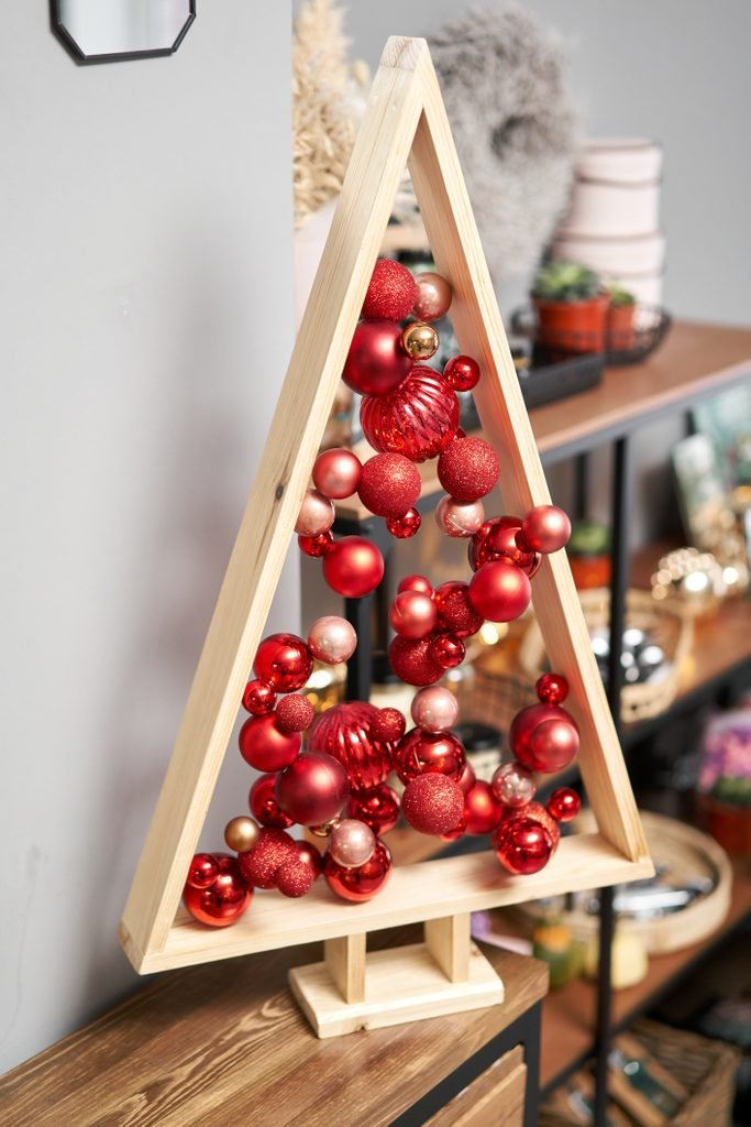 Alternative wooden christmas tree. A handmade Christmas tree and red christmas balls.