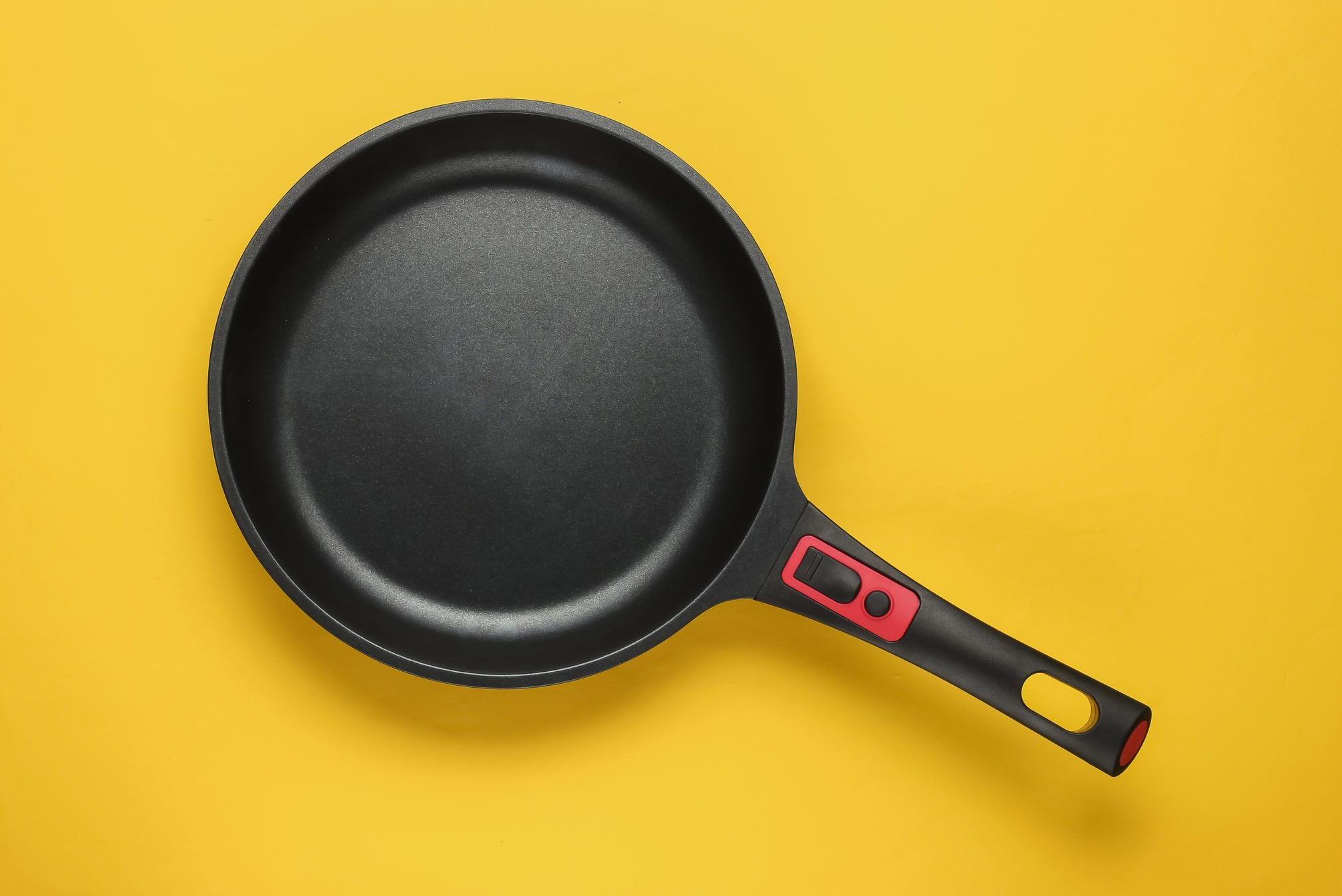 Frying pan with a non-stick coating on yellow background. Cooking minimalism concept. Top view