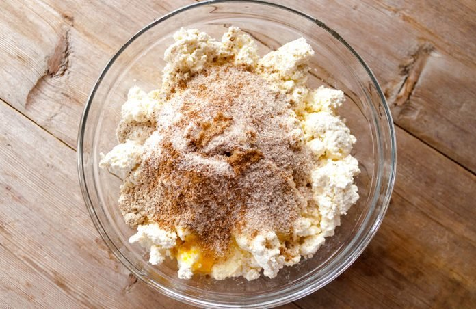 Raw mixture for making cottage cheese cakes in glass bowl on old wooden background