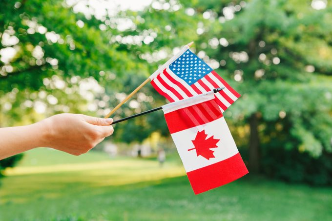 Cropped Hand Of Person Holding two miniature flags: american flag and canadian flag