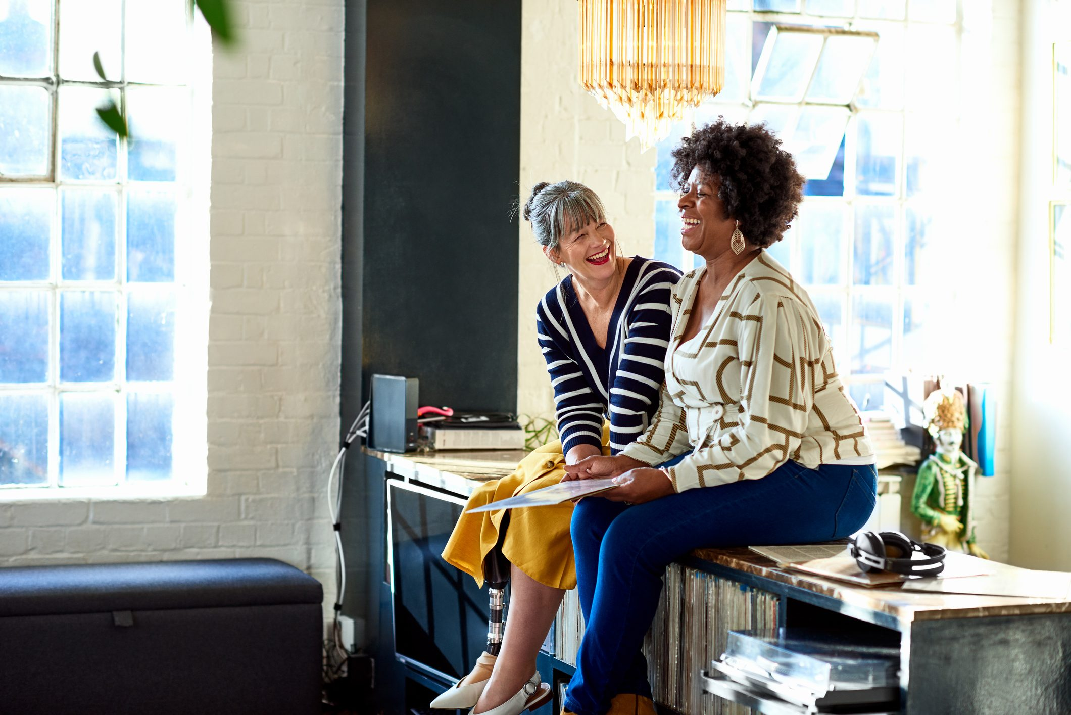 Mature women laughing together in stylish loft apartment