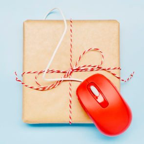 Directly above shot of a small parcel and red computer mouse on blue background