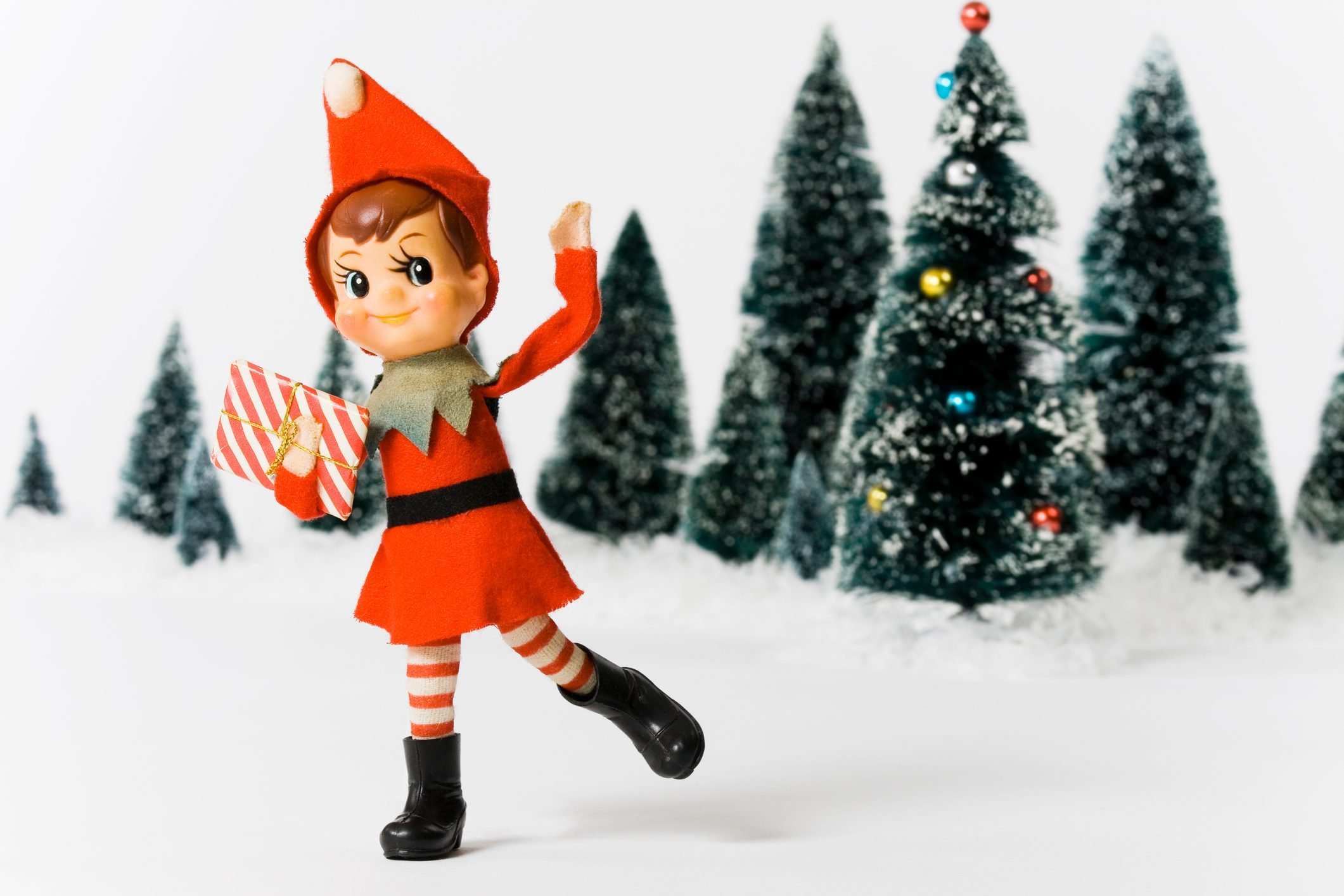 Vintage Christmas doll in front of Christmas trees
