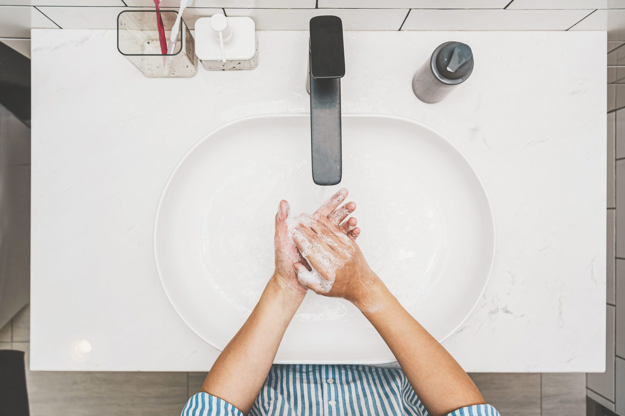 Top view Asian hand washing with faucet water in Bathroom at home
