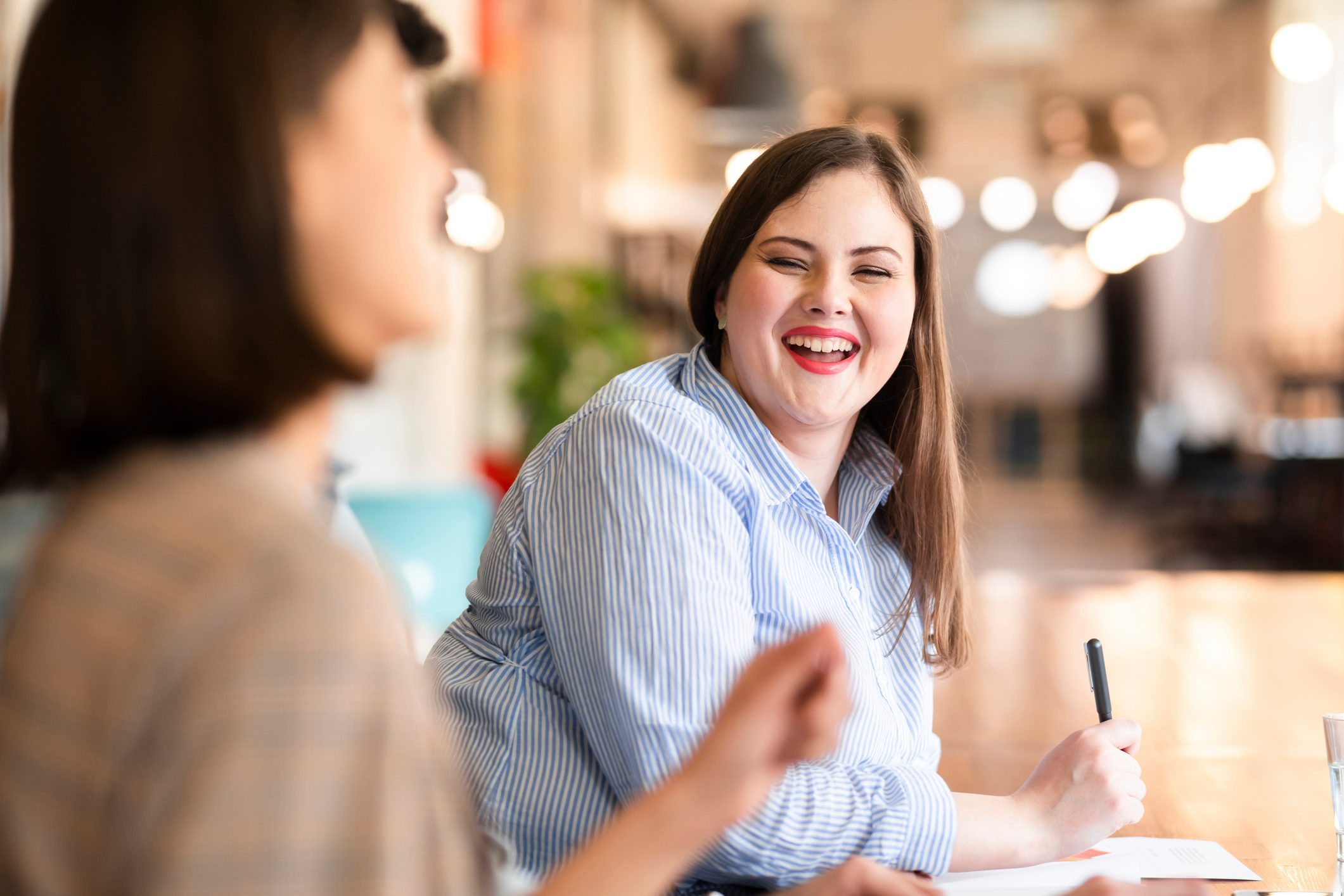 Fun Times at Work: Young Plus Size Businesswoman Sharing a Laugh With a Colleague at the Office