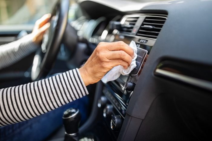 Female hands cleaning and disinfecting her car interior