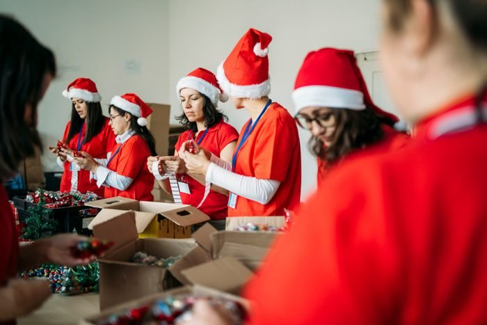 Female charity team during their work by making presents