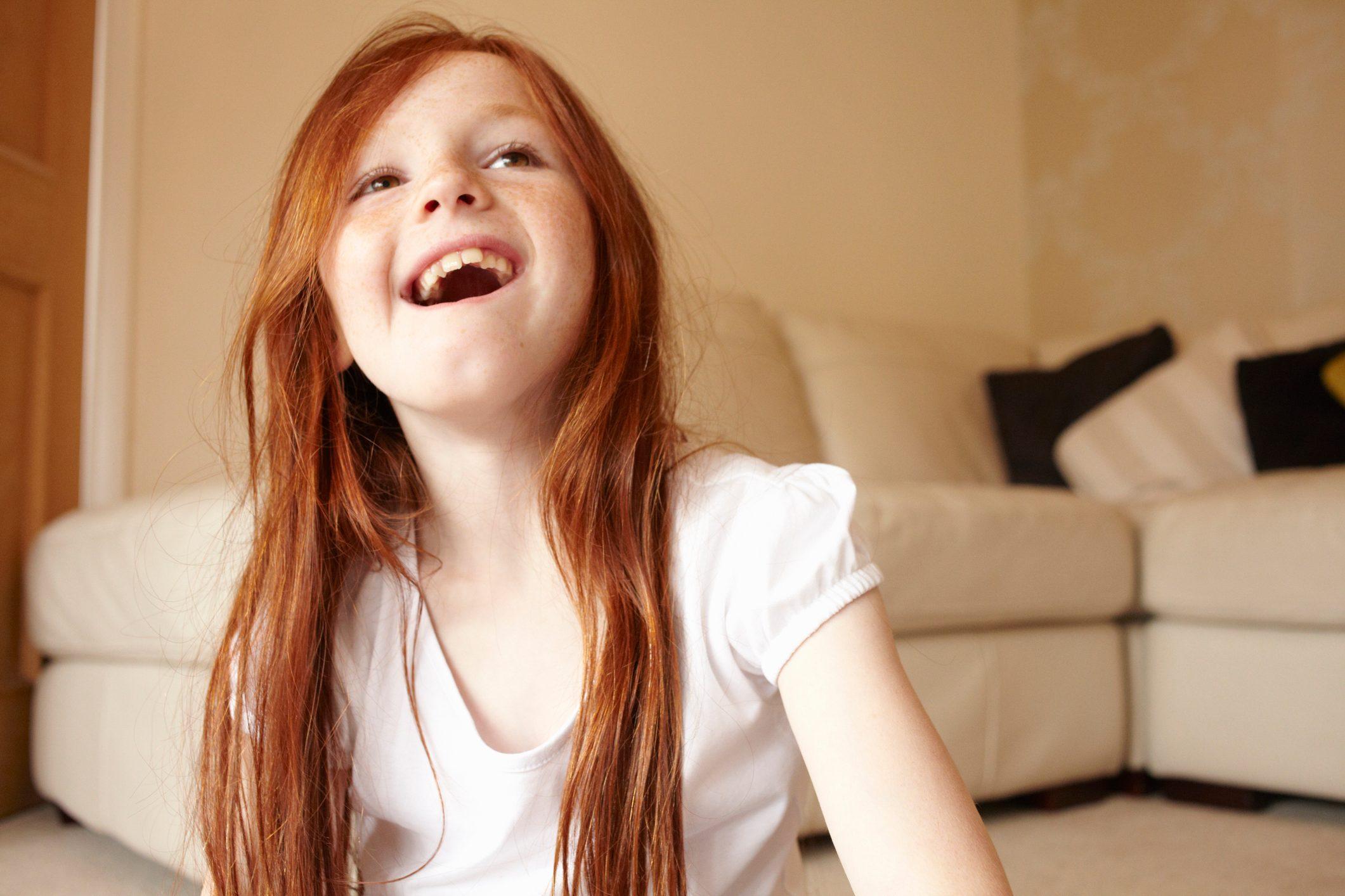 Girl smiling on living room floor