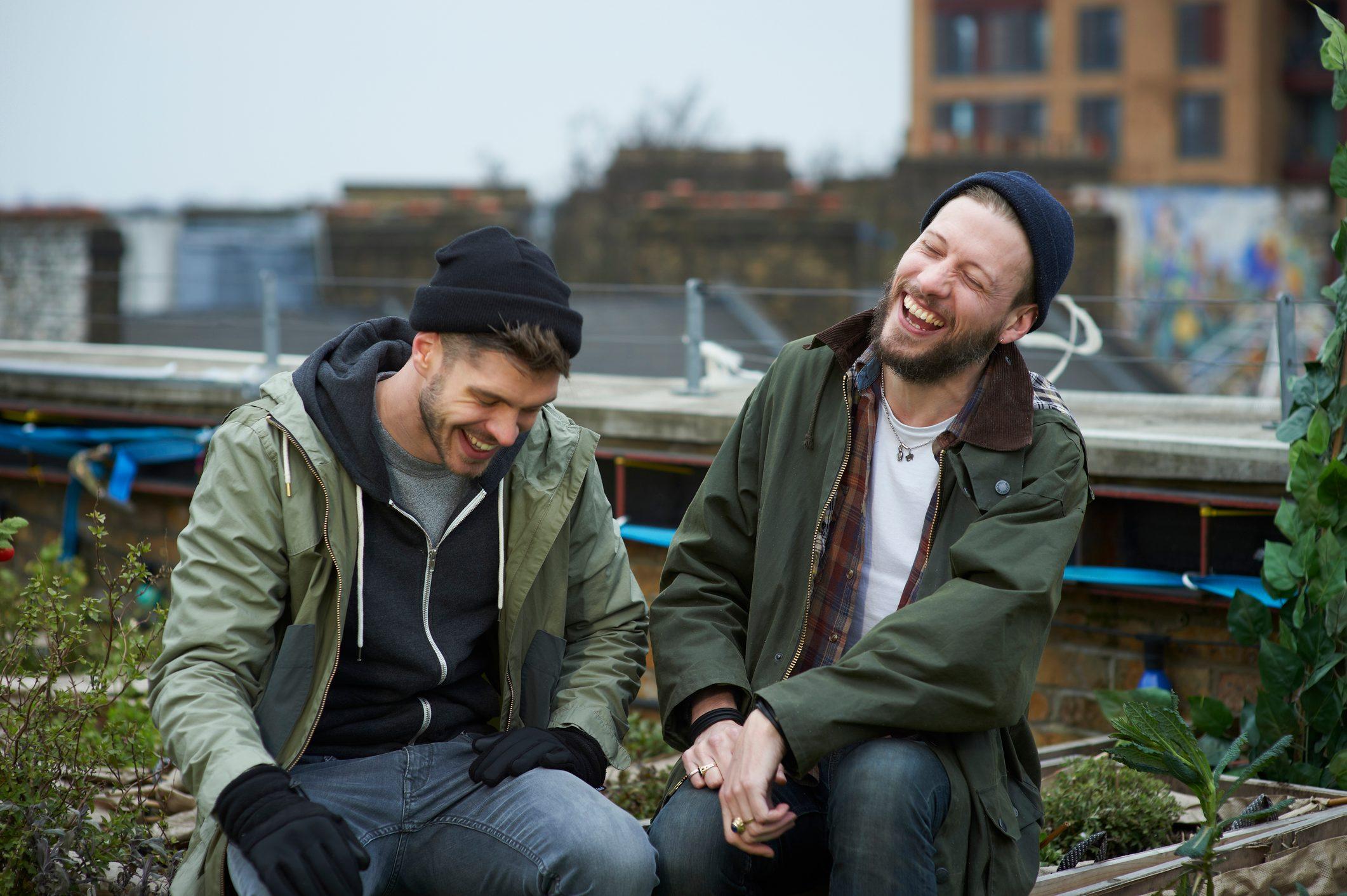 Men sitting in urban roof garden laughing.