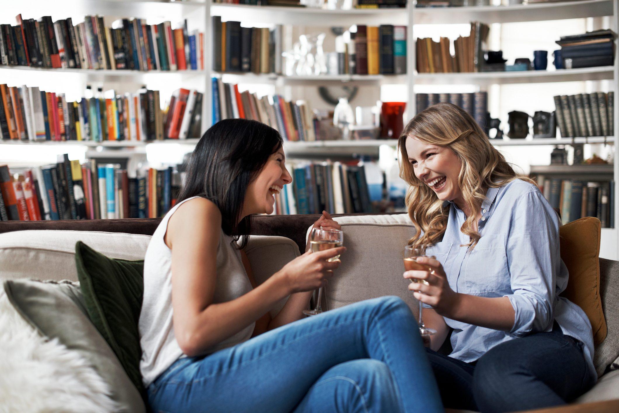 Women sitting on sofa laughing