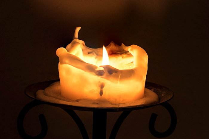 white candle with flame and melting wax, dark background