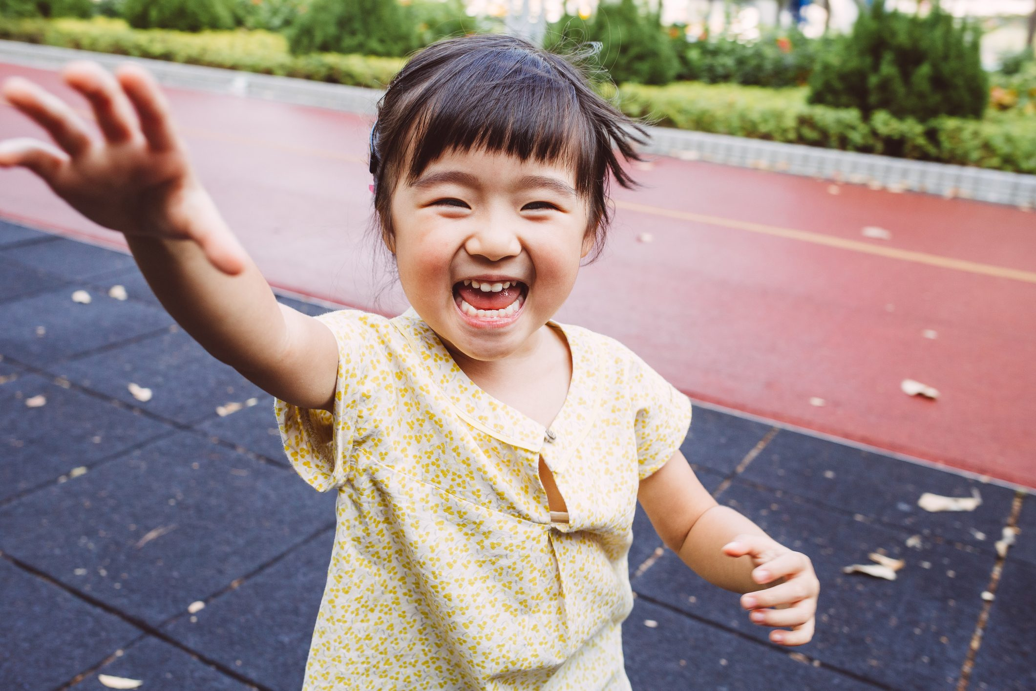 Toddler smiling joyfully at the camera in park