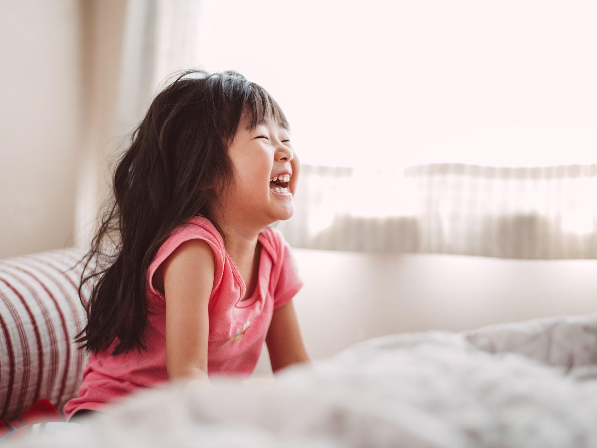 Little girl laughing joyfully in bed