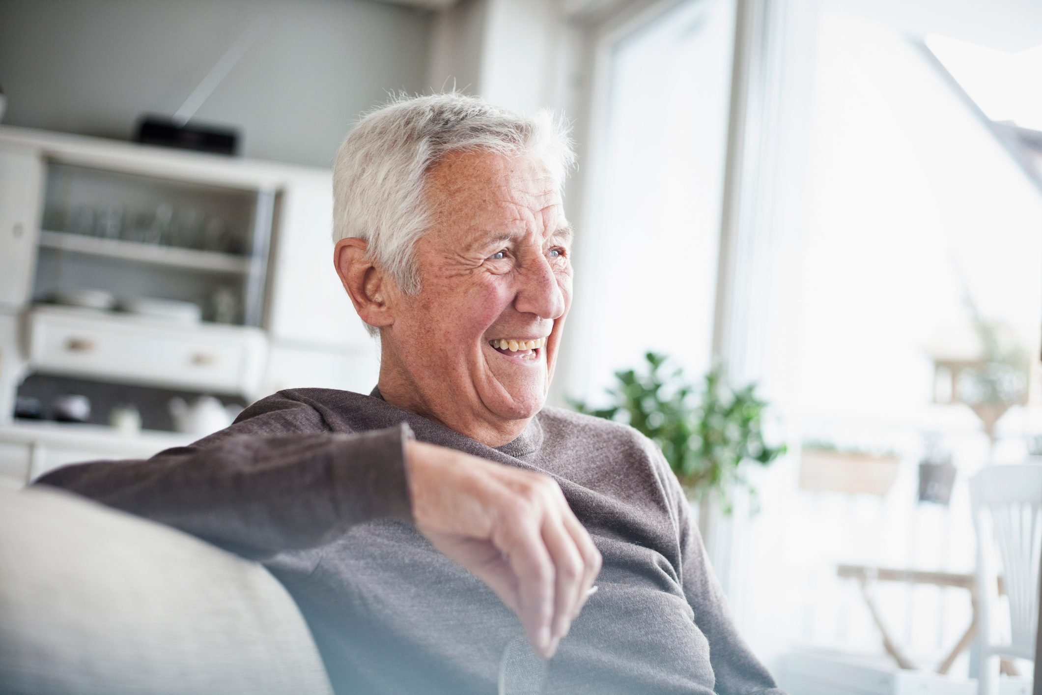 Portrait of laughing senior man sitting on couch at home