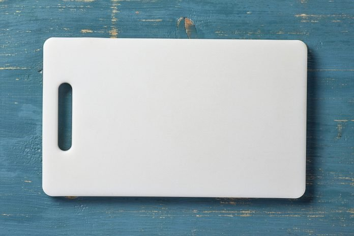 white plastic cutting board on blue wood table