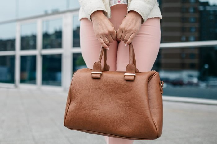 Woman holding handbag in front of office building