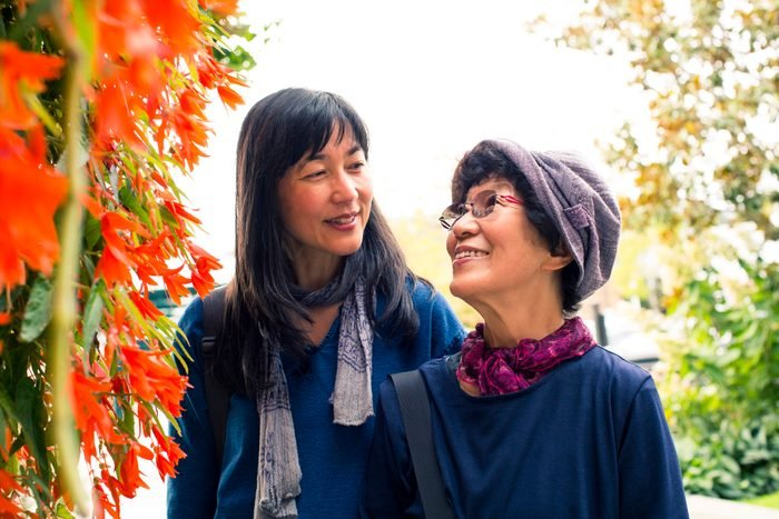Older Japanese mother and daughter near autumn leaves