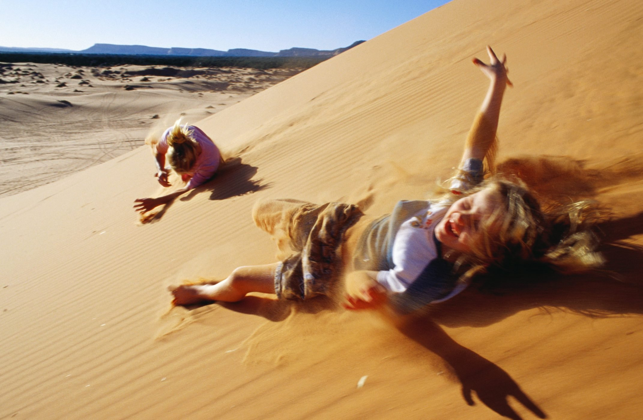 Mother and daughter rolling down sand dunes, Coral Pink Sand Dunes State Park, United States of America