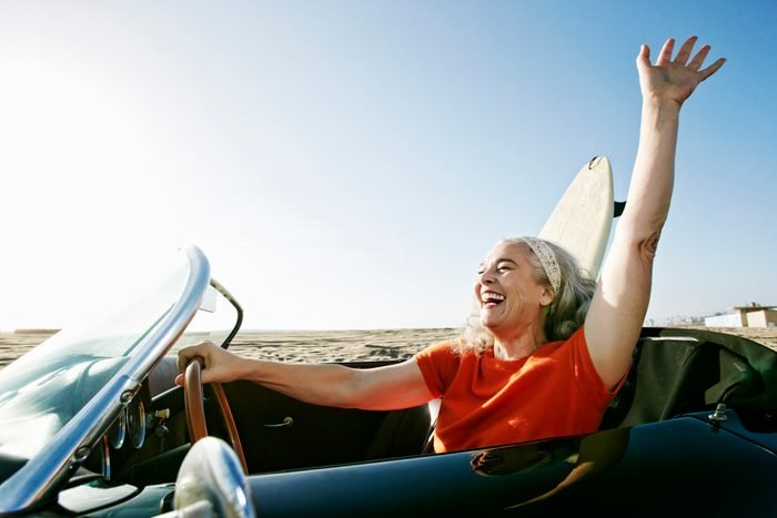 Older Caucasian woman in convertible car with surfboard on beach
