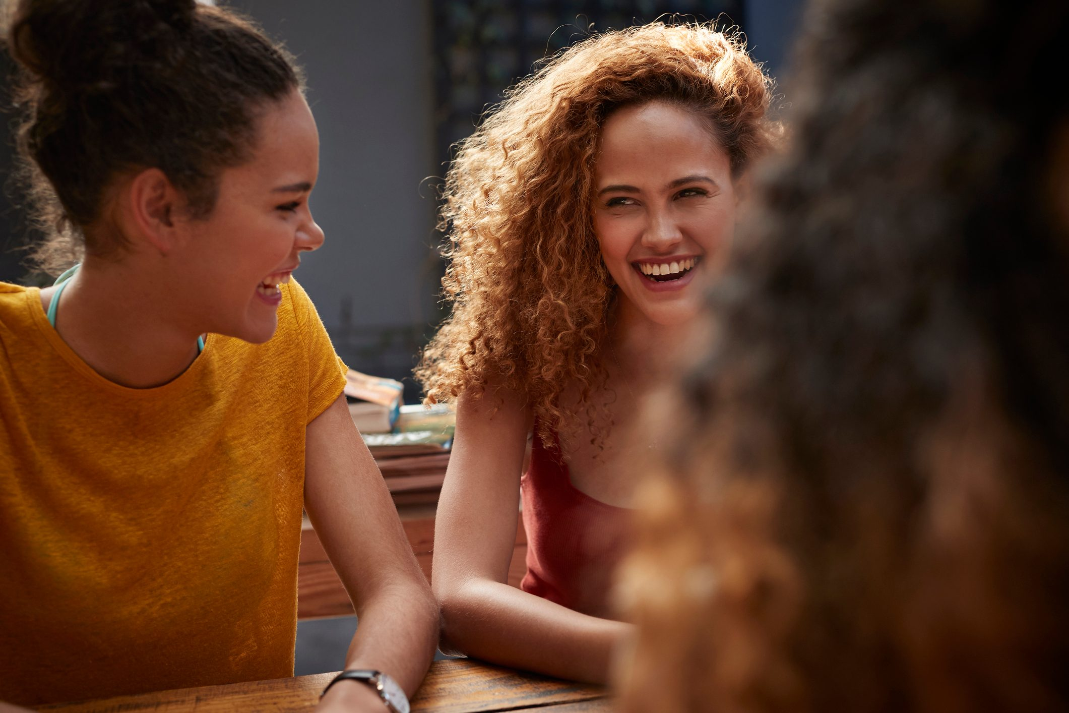 Young women talking and laughing in courtyard of hostel
