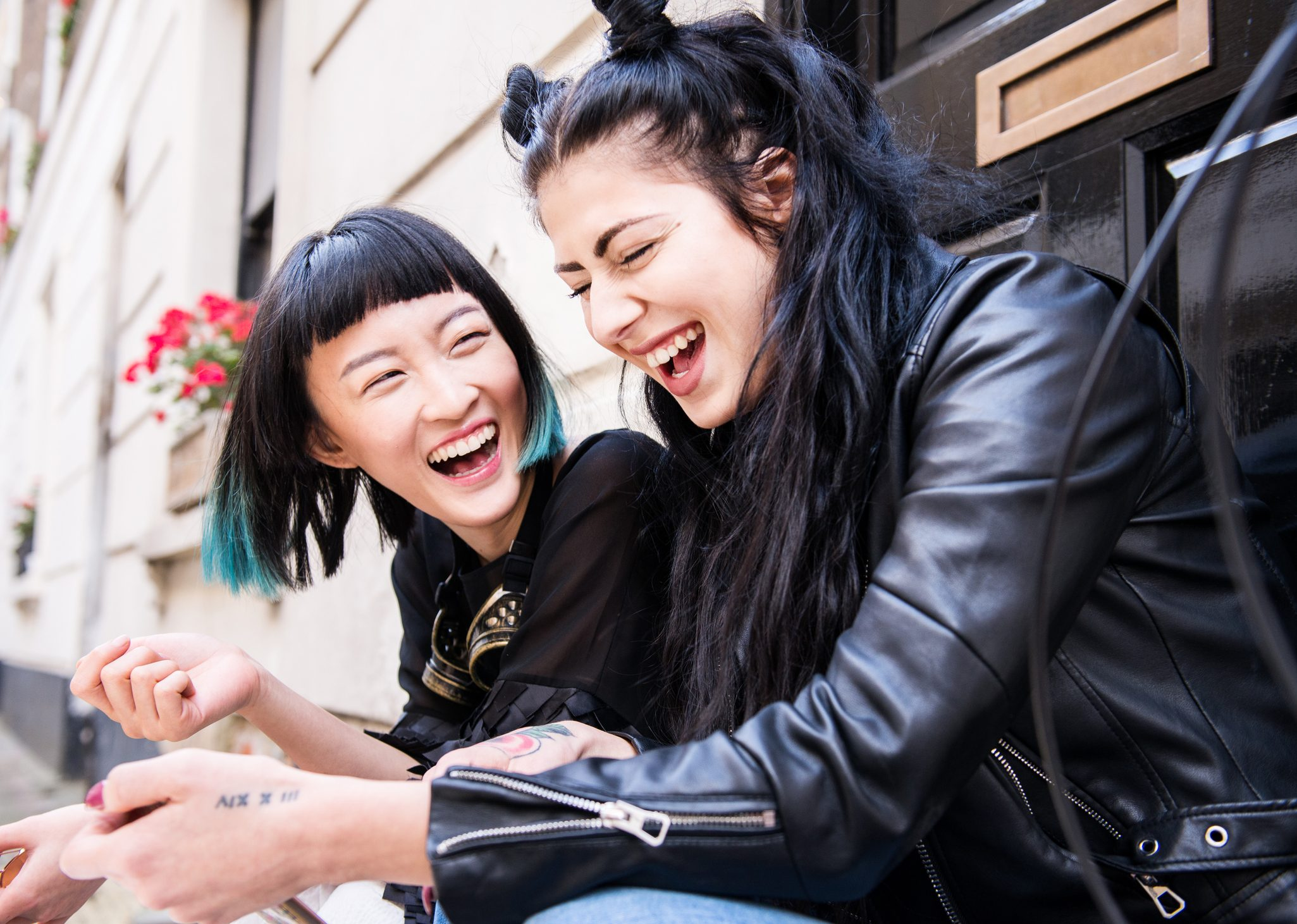 Two young stylish female friends sitting doorstep laughing