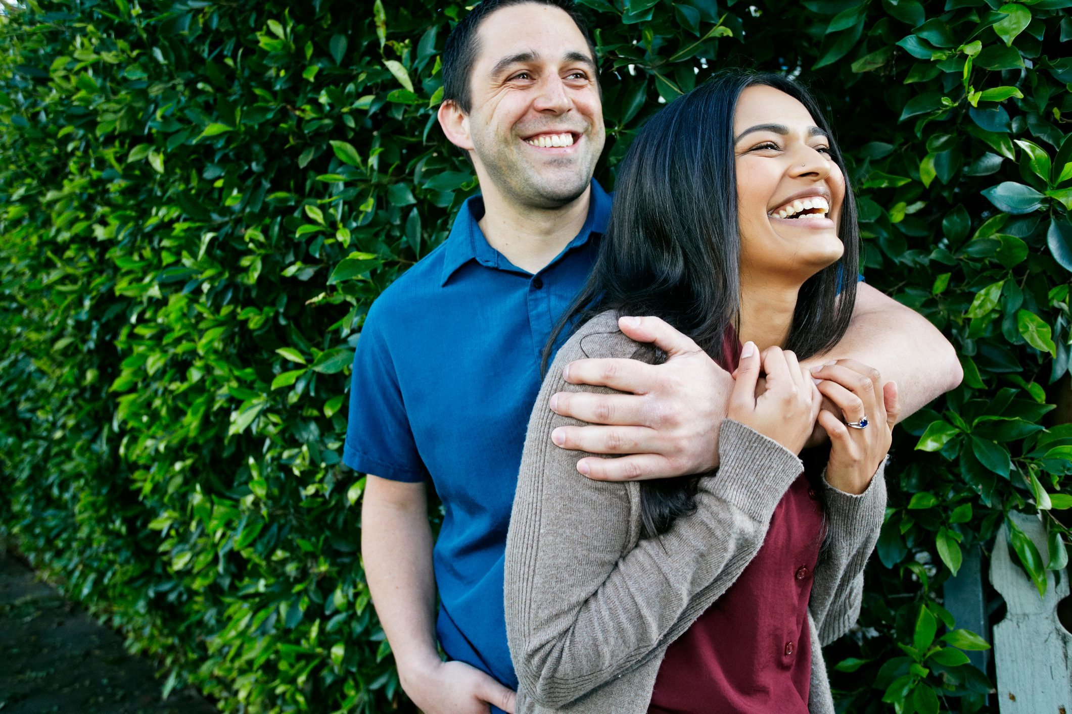 Portrait of smiling couple hugging near leaves