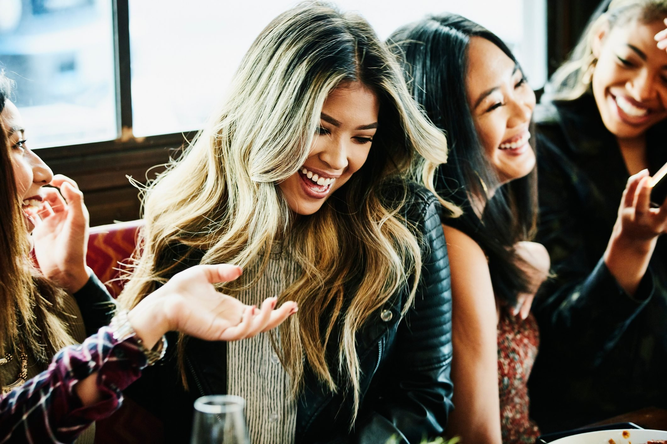 Girl friends laughing together during lunch party