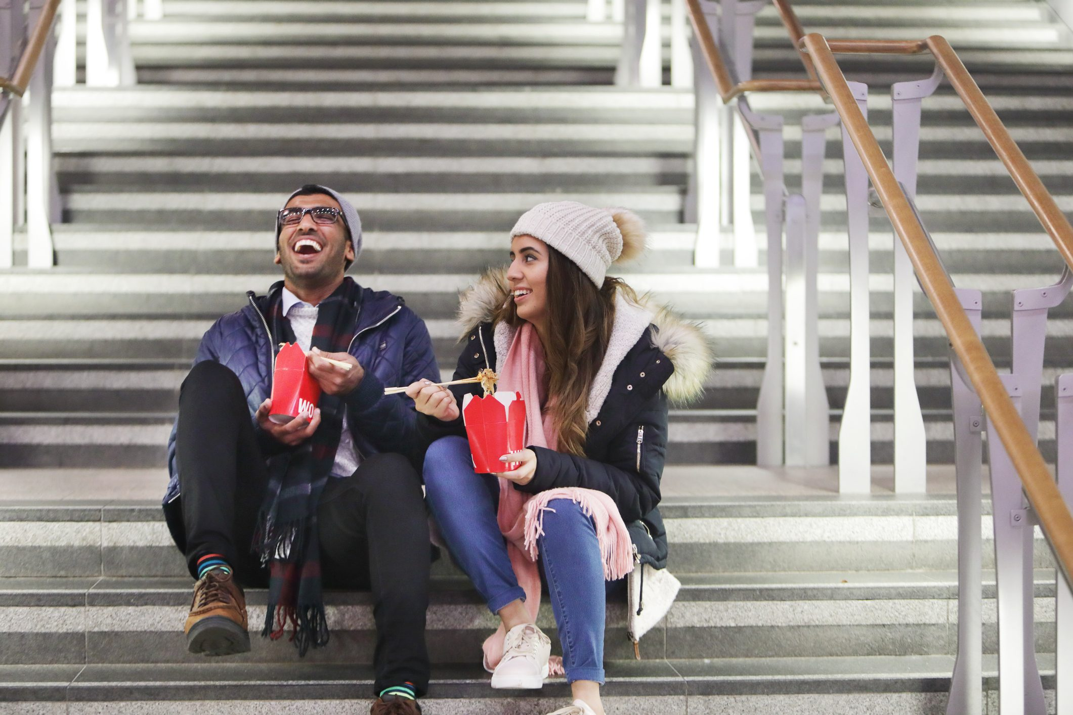 Young couple sat on stair eating take away at night