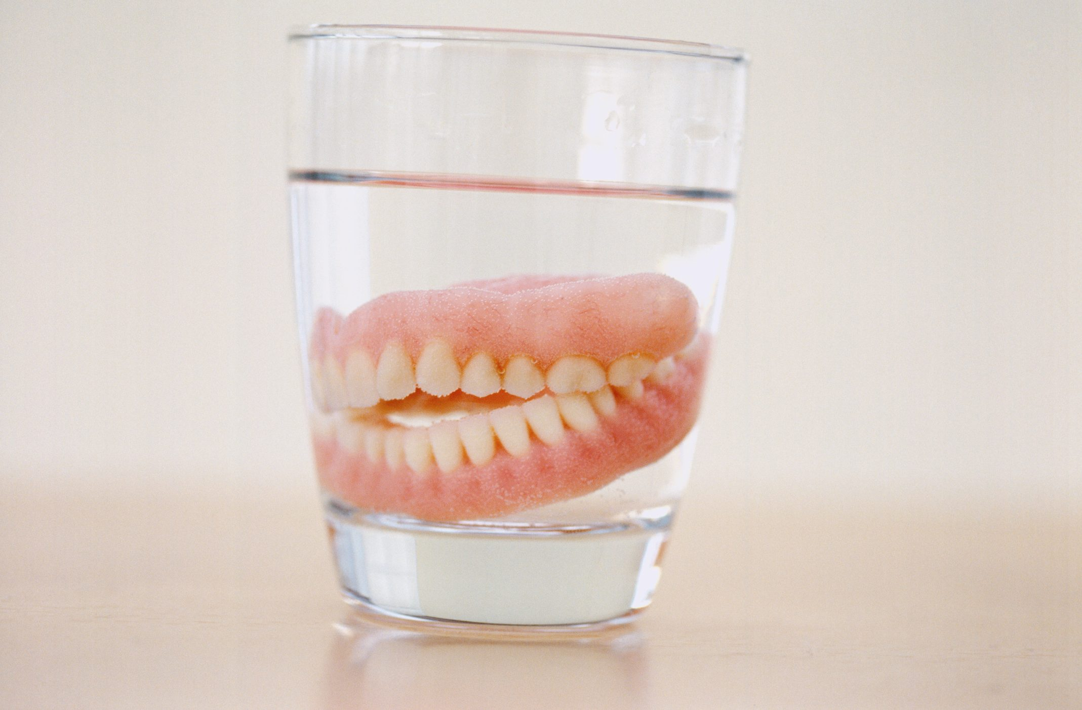 Close-up of a set of dentures in a glass of water