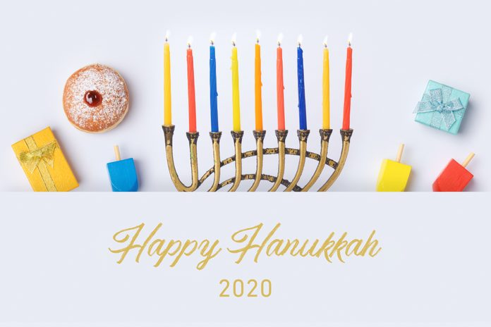 """Jewish holiday Hanukkah flat lay design with menorah, sufganiyot, dreidels, and gifts on white background. Top view from above with text: """"Happy Hanukkah 2020"""""""