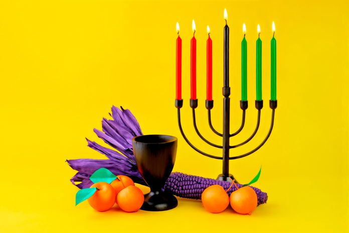 Contemporary Kwanzaa display with corn, apples, candles, and chalice on yellow background.