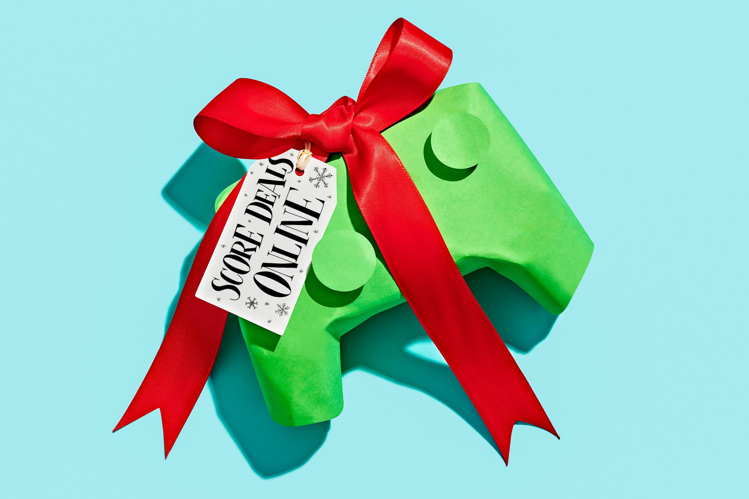 """wrapped video game controller on blue background with gift tag that reads, """"Score deals online"""""""