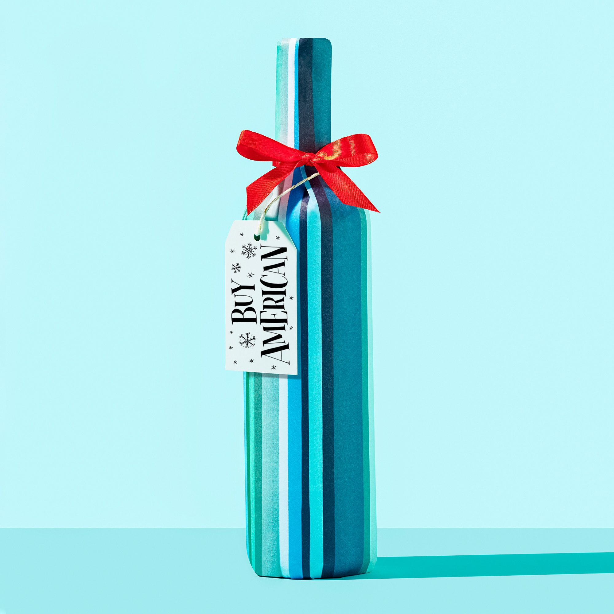 """wrapped wine bottle on blue background with gift tag that reads, """"Buy American"""""""